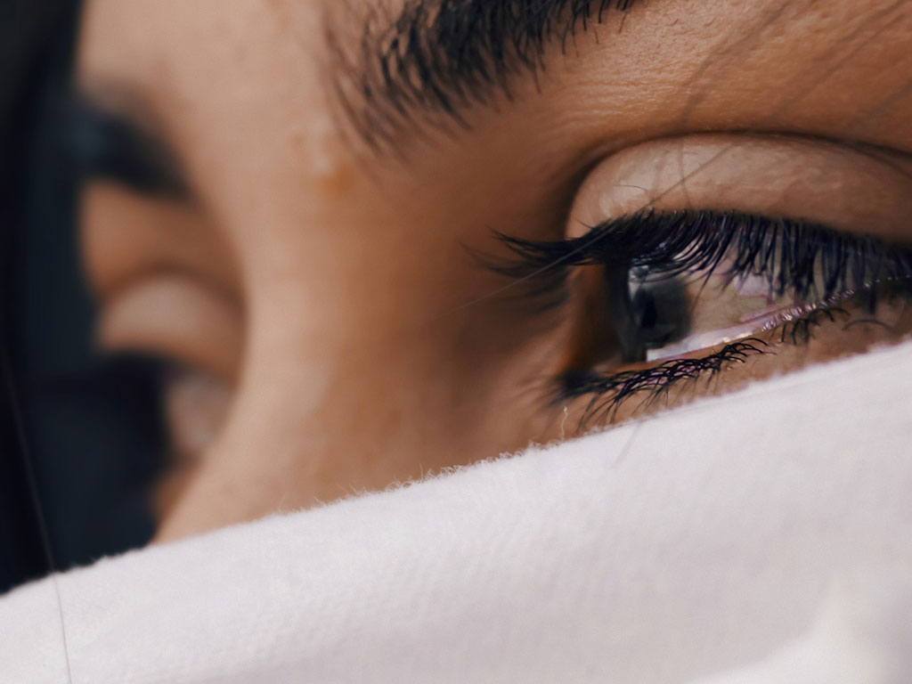Woman with face covering teary eyed